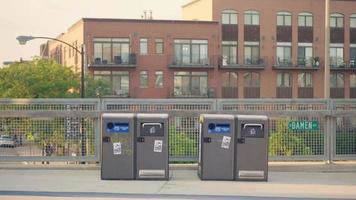 Corredores y ciclistas en pasarela con contenedores de basura. video