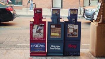 distribuidores de jornais na calçada com trânsito ao fundo