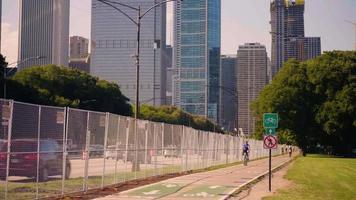 Ciclistas en ciclovía con calles y edificio en segundo plano.