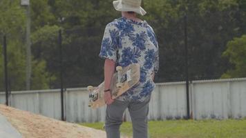 Mann, der mit seinem Skateboard in einem Skatepark weggeht