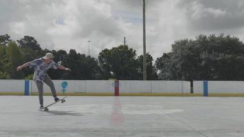 jovem andando de skate sobre duas rodas em um dia ensolarado video
