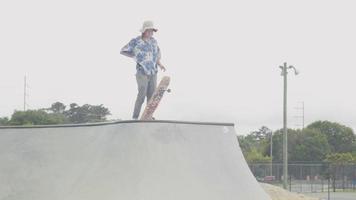 tomada média de um homem pegando seu skate em uma rampa video
