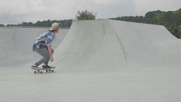 Jeune homme patinant sur une rampe en béton sur une journée ensoleillée video