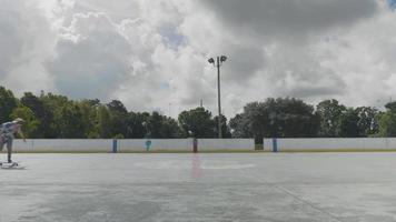 jovem relaxado patinando em uma pista de patinação em um dia ensolarado video