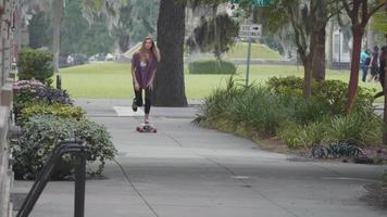 Mujer joven patinando en su longboard en la acera y la calle