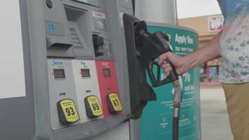 homem no posto de gasolina colocando um bico no distribuidor de combustível