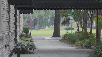 junge Frau auf ihrem Longboard, das sich auf dem Bürgersteig entfernt