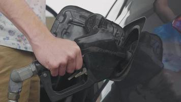 Man In Station Filling The Gas Tank Of  His Car