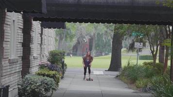 junge Frau auf ihrem Longboard nähert sich auf dem Bürgersteig