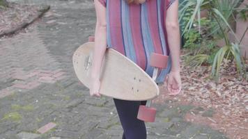 Foto de viaje de una mujer caminando y sosteniendo su longboard