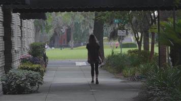 mujer caminando por la acera y sosteniendo su longboard