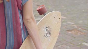 detalhe de uma jovem caminhando e segurando seu longboard