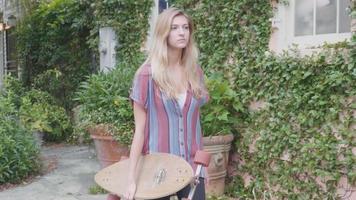 mujer seria caminando y sosteniendo su longboard