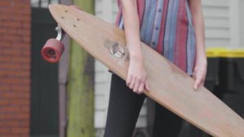 Detalle de piernas y brazos de mujer joven sosteniendo su longboard