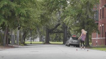 mujer joven en su longboard cruzando la calle