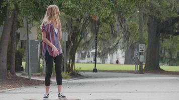 mujer joven en el cruce de la calle en su longboard