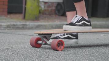 Nahaufnahme von Frauenfüßen, die ihr Longboard schieben
