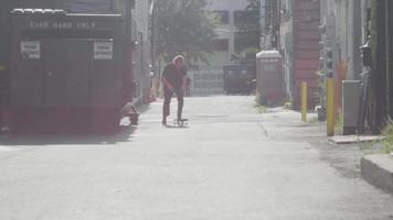 bärtiger Mann in der Gasse nähert sich und macht Skateboard-Tricks