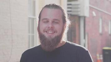 hombre barbudo mirando a la cámara y sonriendo