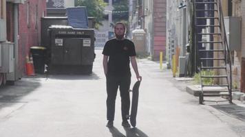 bärtiger Mann in der Gasse drehte sein Skateboard und ließ es fallen