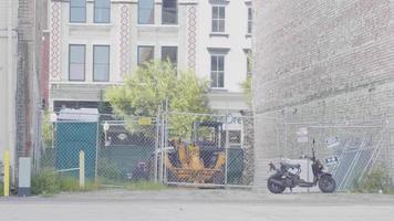 bärtiger Mann, der auf Bürgersteig mit Gebäuden im Hintergrund skatet