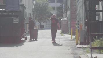 bärtiger Skater nähert sich auf seinem Skateboard in der Gasse