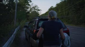 velhinha colocando roupas em seu carro em câmera lenta video