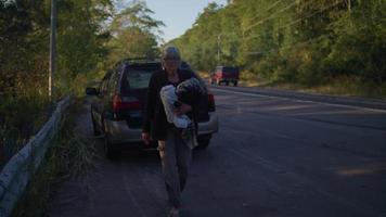 oude dame die kleren uit haar auto pakt