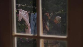senhora pegando roupas e colocando em seu cesto de roupa suja