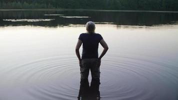 foto média de uma senhora entrando no lago video