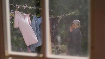 vecchia signora raccogliendo maglioni al rallentatore