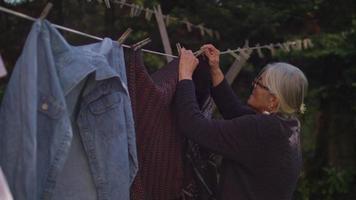 velhinha pendurando suéteres em câmera lenta video