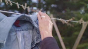 close-up de velhinha pendurando roupas em câmera lenta video