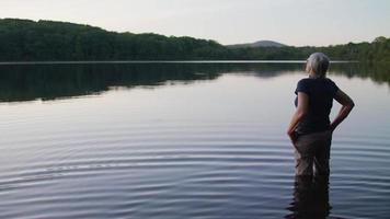 senhora idosa no lago observando a floresta com humor pensativo video