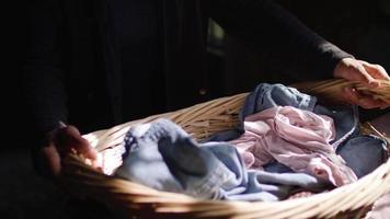 Cerca de la anciana colocando su canasta de lavandería en su cama