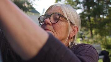 Close up della vecchia signora che raccoglie i vestiti nel suo giardino