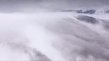 Dron footage over a winter foggy mountain
