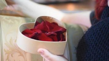 regalo de San Valentín. niña abriendo caja de regalo corazón con pétalos de rosa video