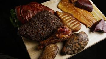 Rotating shot of a variety of delicious, premium smoked meats on a wooden cutting board - FOOD 050