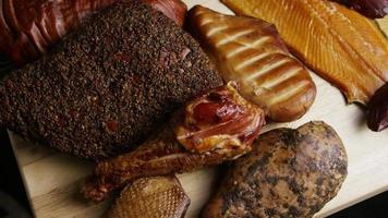 Rotating shot of a variety of delicious, premium smoked meats on a wooden cutting board - FOOD 057