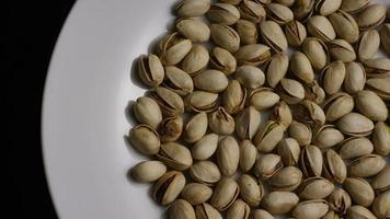 Cinematic, rotating shot of pistachios on a white surface - PISTACHIOS 003