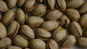 Cinematic, rotating shot of pistachios on a white surface - PISTACHIOS 007