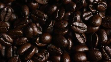 Rotating shot of delicious, roasted coffee beans on a white surface - COFFEE BEANS 058