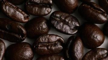 colpo rotante di deliziosi chicchi di caffè tostati su una superficie bianca - chicchi di caffè 034
