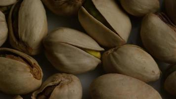 Cinematic, rotating shot of pistachios on a white surface - PISTACHIOS 008