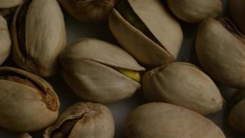 colpo cinematografico e rotante di pistacchi su una superficie bianca - pistacchi 008 video