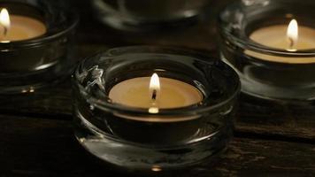 Velas de té con mechas en llamas sobre un fondo de madera - velas 006