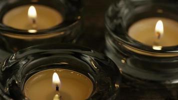 Velas de té con mechas en llamas sobre un fondo de madera - velas 018