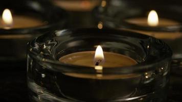 Velas de té con mechas en llamas sobre un fondo de madera - velas 023