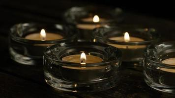 Velas de té con mechas en llamas sobre un fondo de madera - velas 021